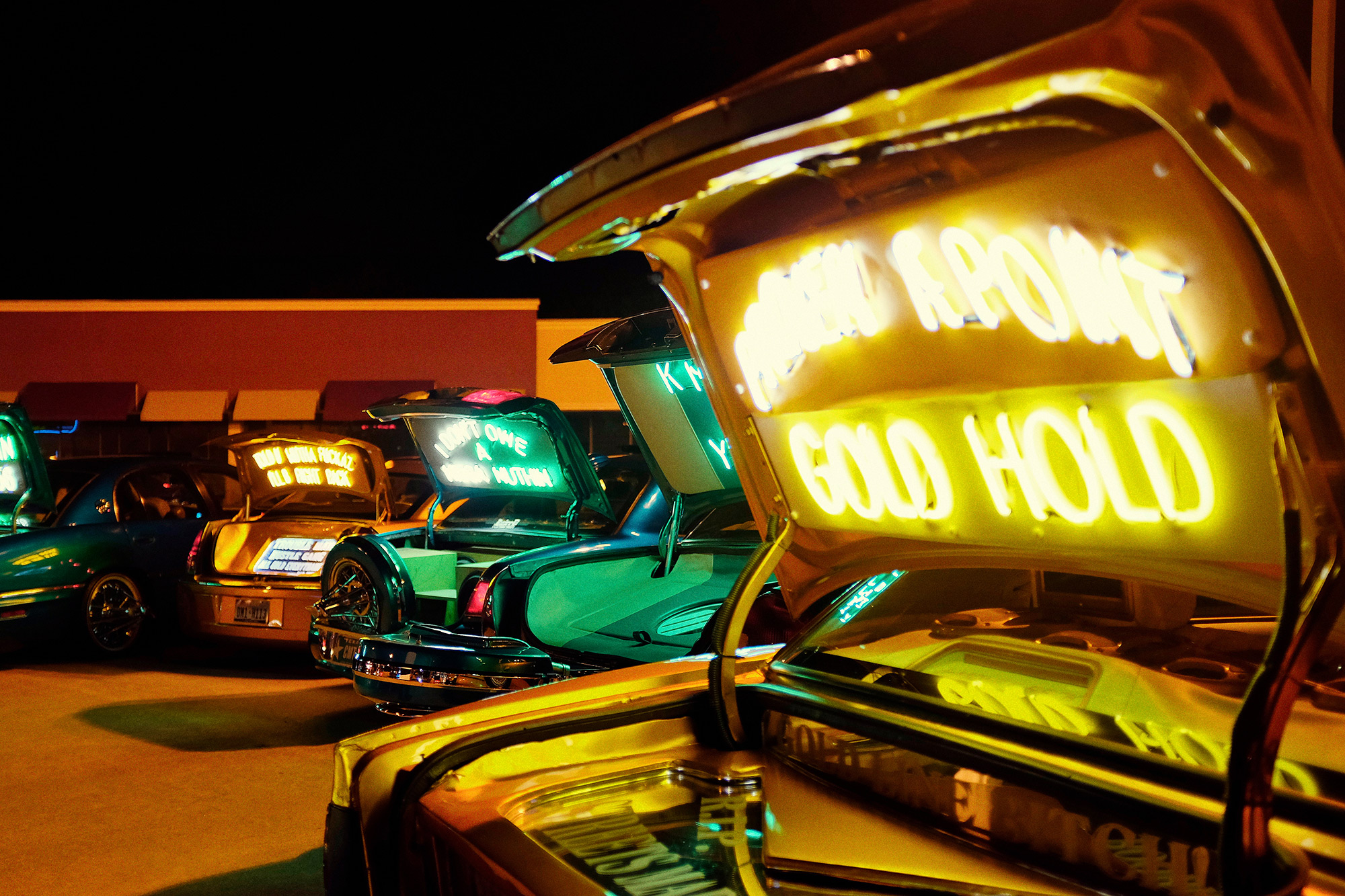 Slabs outfitted with neon signs and messages parked outside of Southside Smoke Shop in Houston, Texas during a music video featuring Bun B, Paul Wall and Trae tha Truth, photographed by Houston editorial and commercial photographer, Todd Spoth.