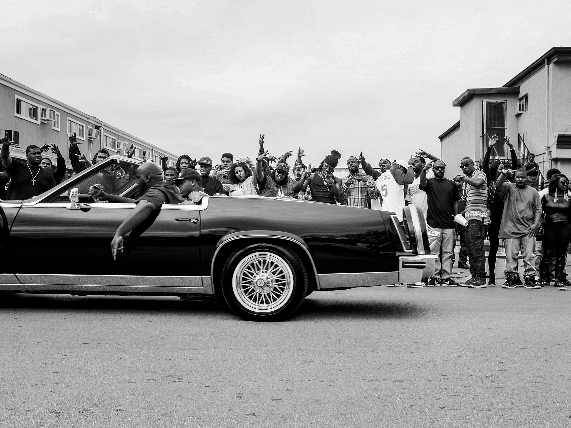 "A Slab passes by a crowd of people during the filming of a music video for ""Show the World"" by Lil Boosie and Webbie, in the 5th ward of Houston, Texas, photographed by Todd Spoth."