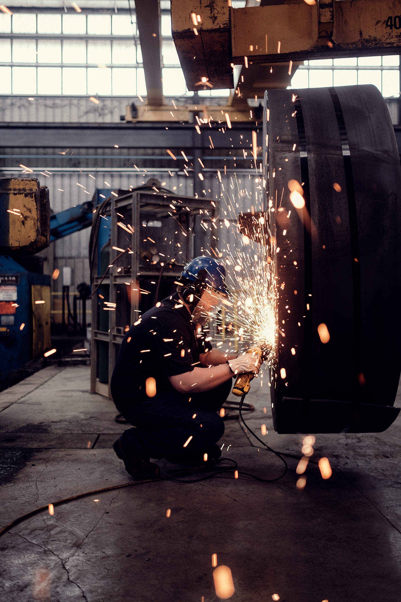 An industrial welder is photographed on location in Houston, Texas in a steel plant, by photographer, Todd Spoth.