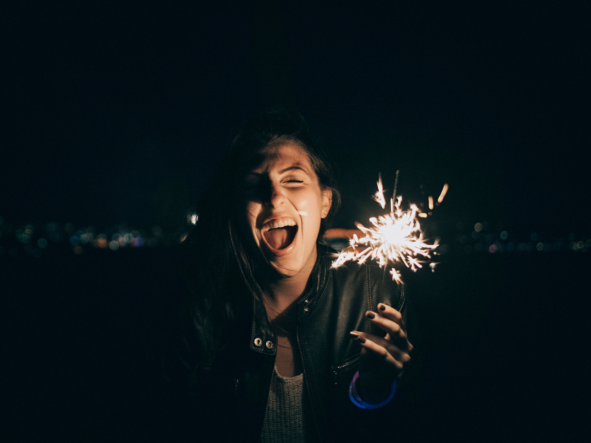 A girl holds a lit sparkler during a New Year