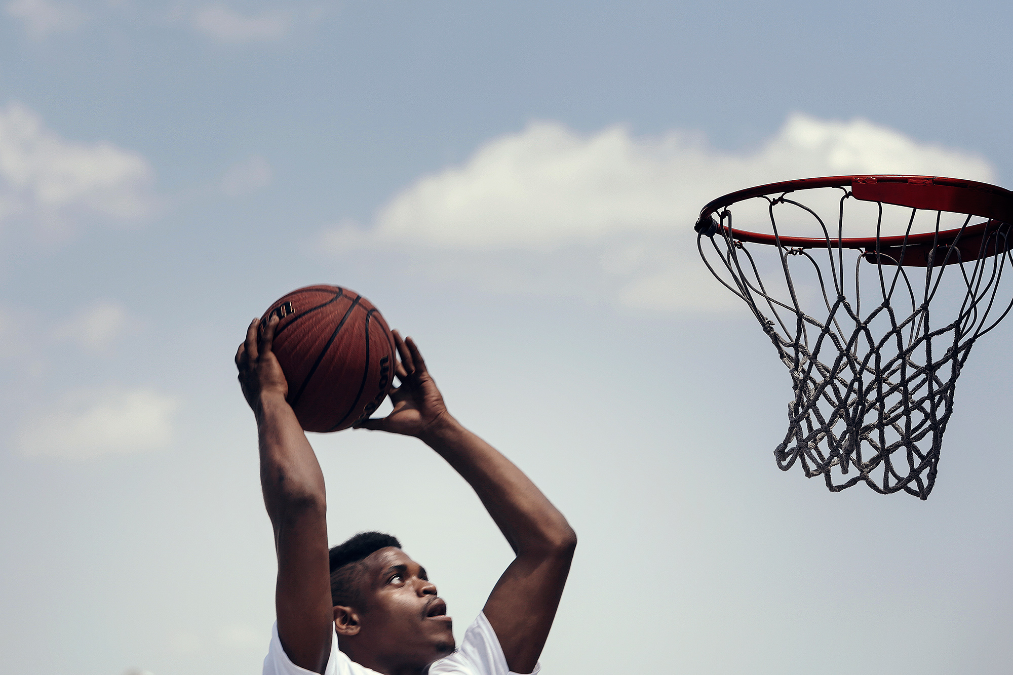 A street ball player goes up for a dunk, photographed by lifestyle photographer, Todd Spoth.