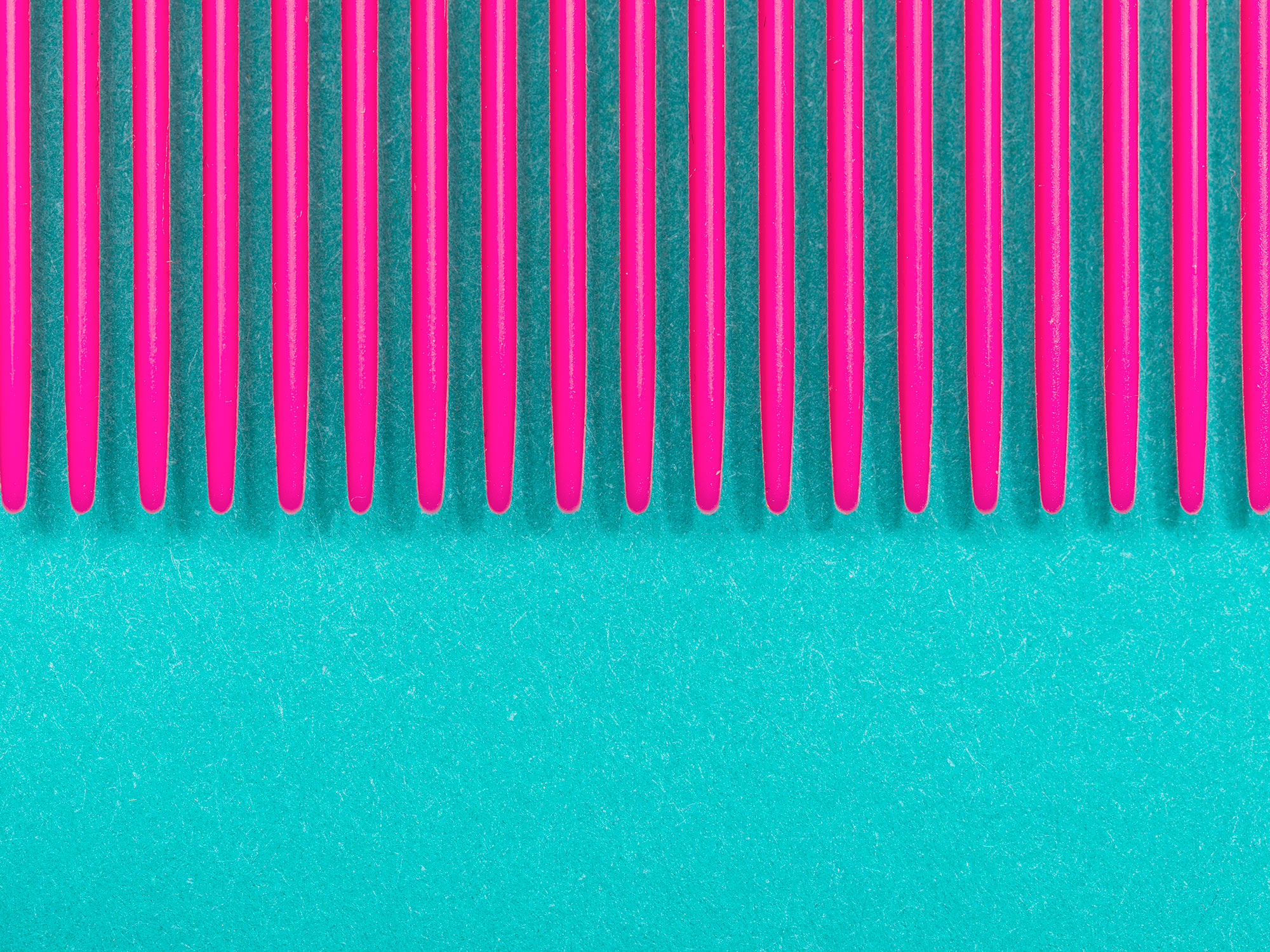 Detail photograph of a pink comb on teal paper, photographed by commercial photographer Todd Spoth.