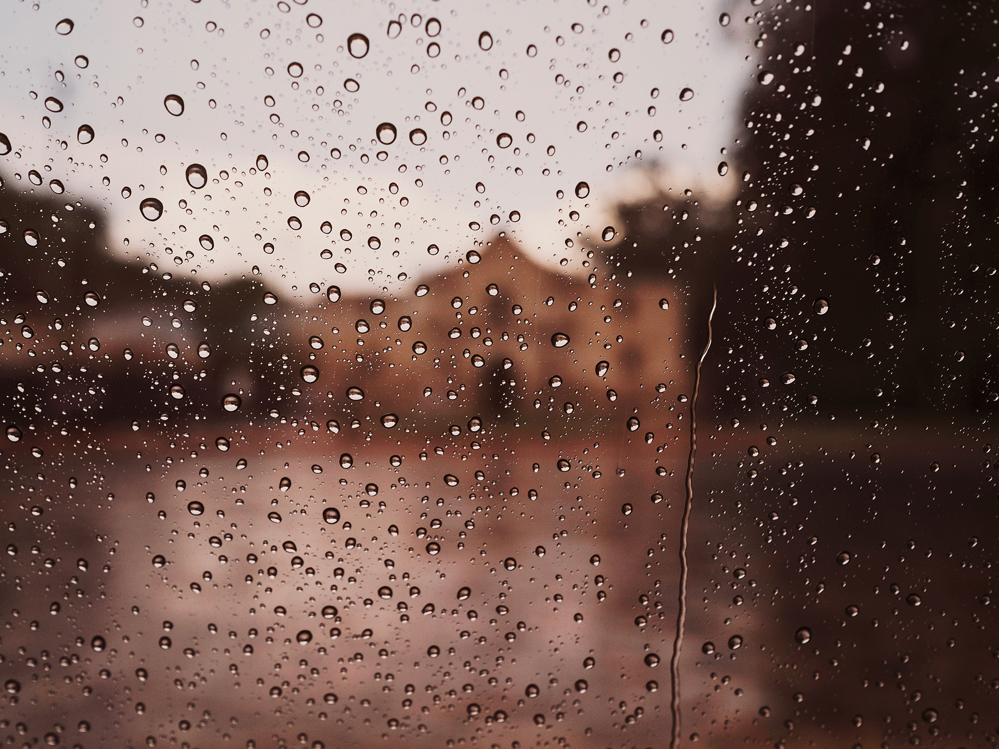 A detail photograph of a window with rain drops showing The Alamo in San Antonio, Texas in the background, by Todd Spoth.
