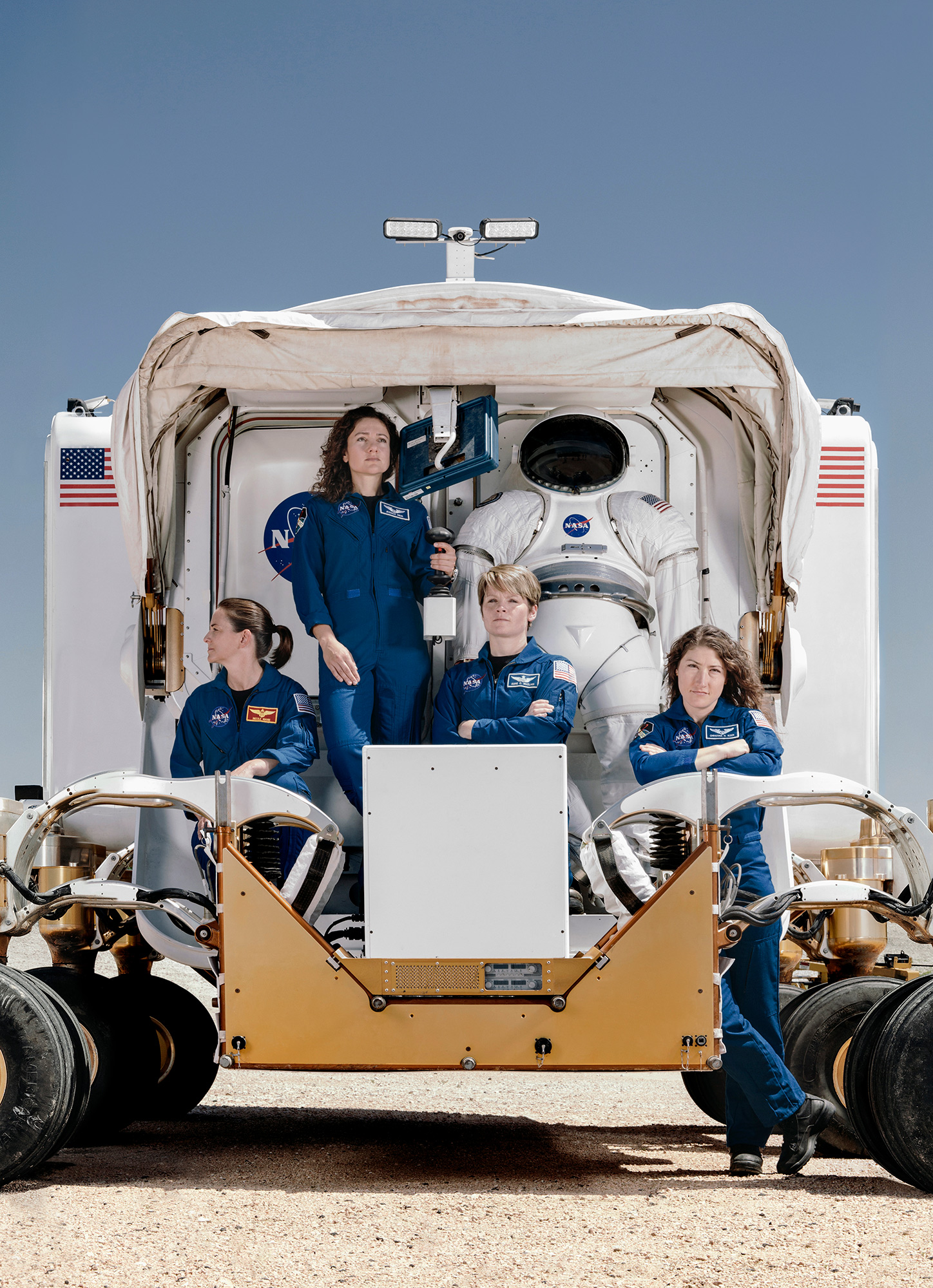Christina Koch, Nicole Mann, Anne McClain and Jessica Meir, NASA astronauts, posed on the rear of the mars rover vehicle, photographed by Todd Spoth.